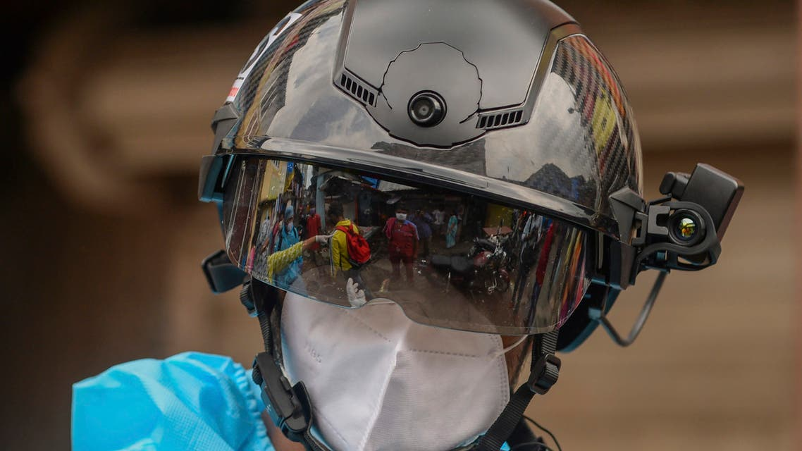 A volunteer health worker of the Non-Governmental Organization (NGO) Bharatiya Jain Sanghatana (BJS) wearing Personal Protective Equipment (PPE) using a smart helmet equipped with a thermo-scan sensor checks the body temperature of residents during a door-to-door medical screening drive for the COVID-19 coronavirus, at a residential area in Mumbai on July 21, 2020. India on July 17 hit a million coronavirus cases, the third-highest total in the world, with no sign yet of the infection curve flattening as new cases emerge in rural areas. More than 25,000 people have died nationally.