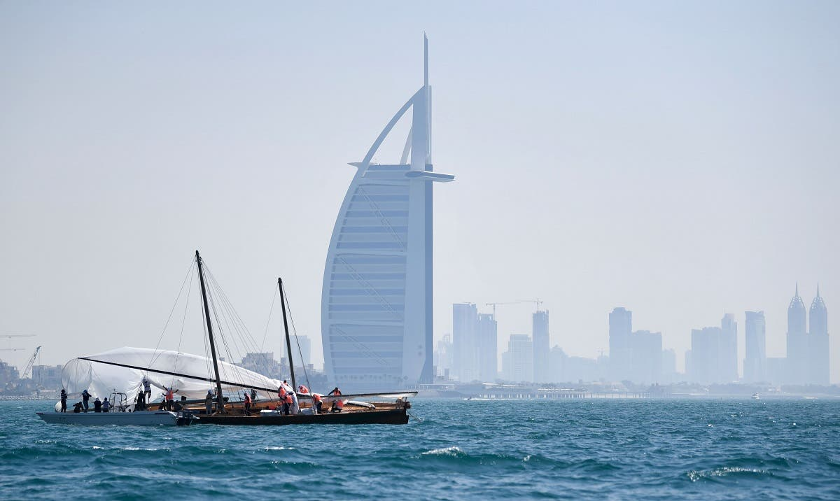 The crew of a competing boat in the annual long-distance 60ft Dubai Traditional Dhow Sailing Race, work on the sail across from Burj Al Arab. (File photo: AFP)