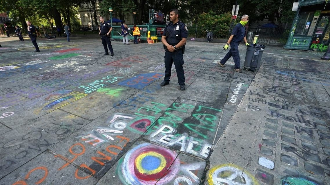 New York police officers standby as sanitation workers remove graffiti at the site of Occupy City Hall protest on July 22, 2020, in New York. (AFP)