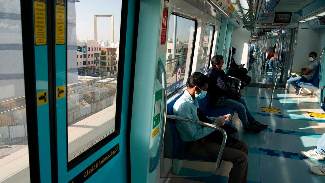 A commuter wearing a mask and disposable gloves to help curb the spread of the coronavirus, checks his phone aboard the driverless Metro. (AP)