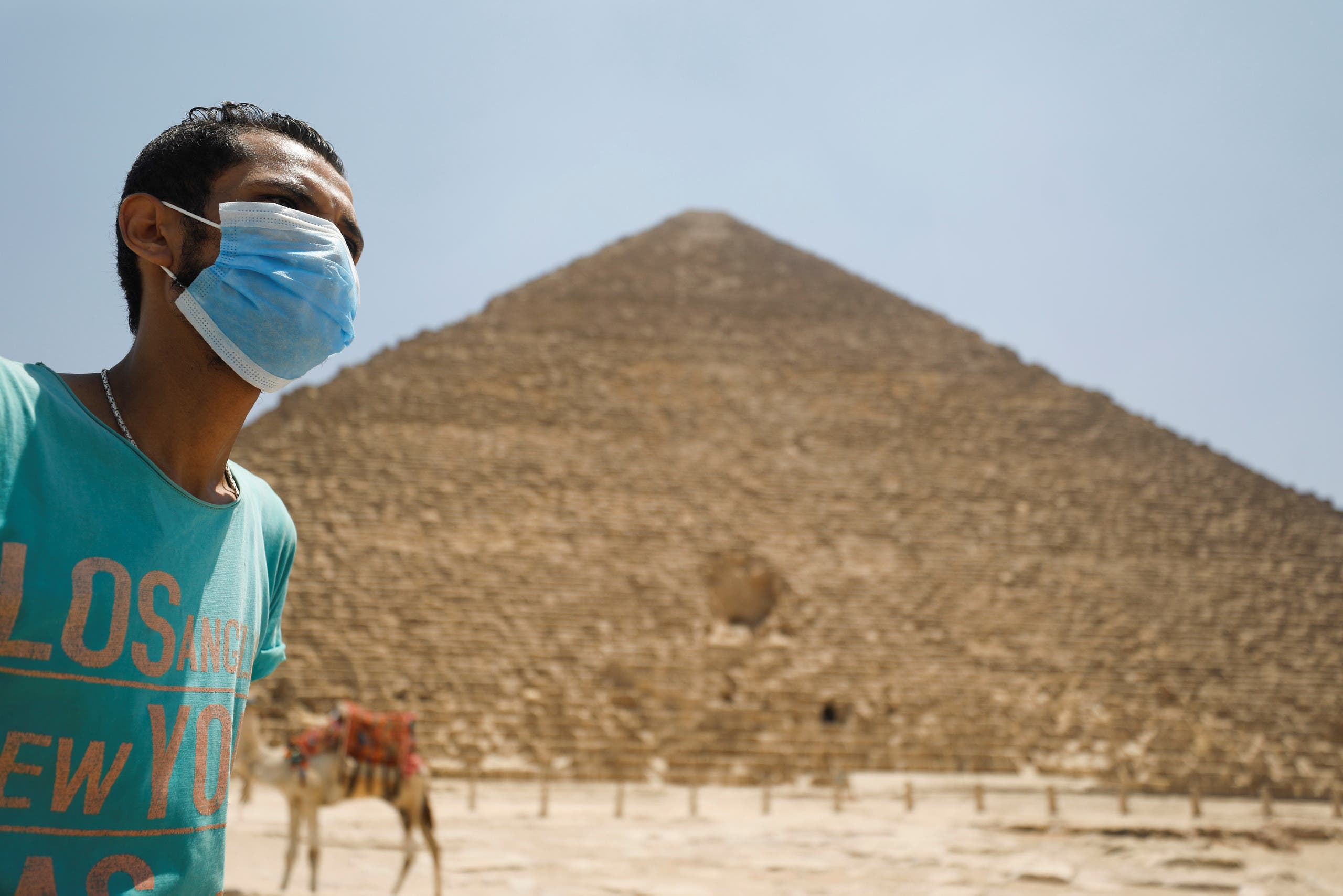 A man wearing a face mask is seen in front of the Great Pyramids of Giza after reopening for tourist visits, following the outbreak of the coronavirus disease (COVID-19), in Cairo, Egypt July 1, 2020. (Reuters)