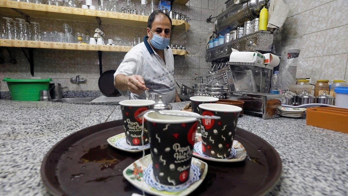 A waiter serves customers in a cafe after months of lockdown, following the outbreak of the coronavirus disease (COVID-19), in Cairo, Egypt, June 27, 2020. (Reuters)