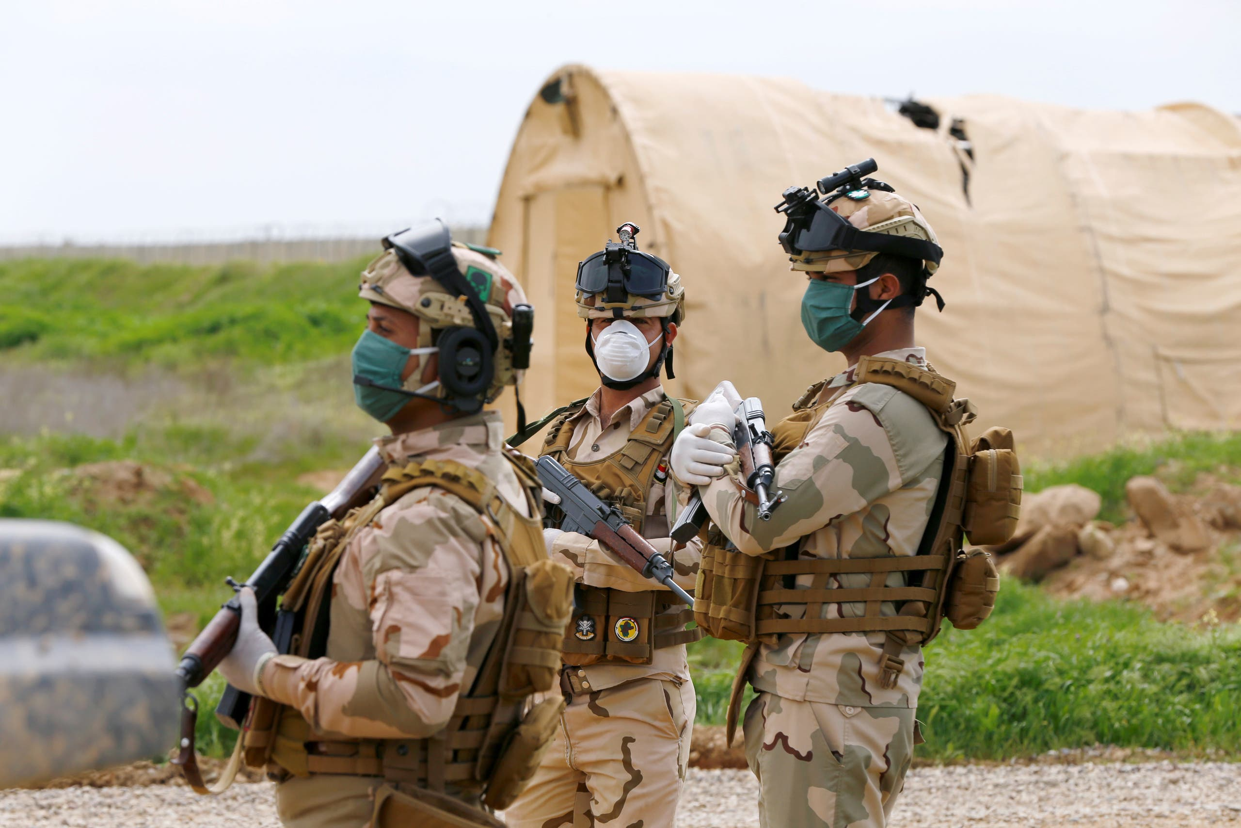 Iraqi soldiers wear protective face masks, following the outbreak of coronavirus disease (COVID-19), as they stand guard during the hand over of Qayyarah Airfield West from US-led coalition forces to Iraqi Security Forces, in the south of Mosul, Iraq March 26, 2020. (Reuters)