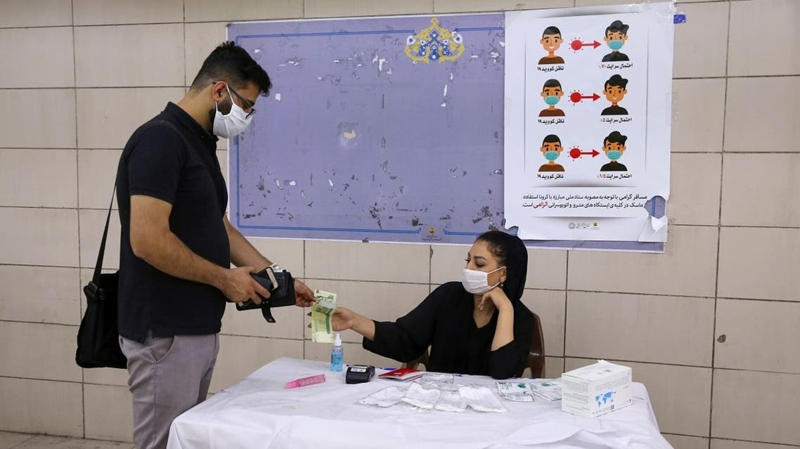 An Iranian man, wearing a protective face mask, buys hand sanitiser from a woman at a metro station in the capital Tehran on July 22, 2020, during the COVID-19 epidemic. (AFP)
