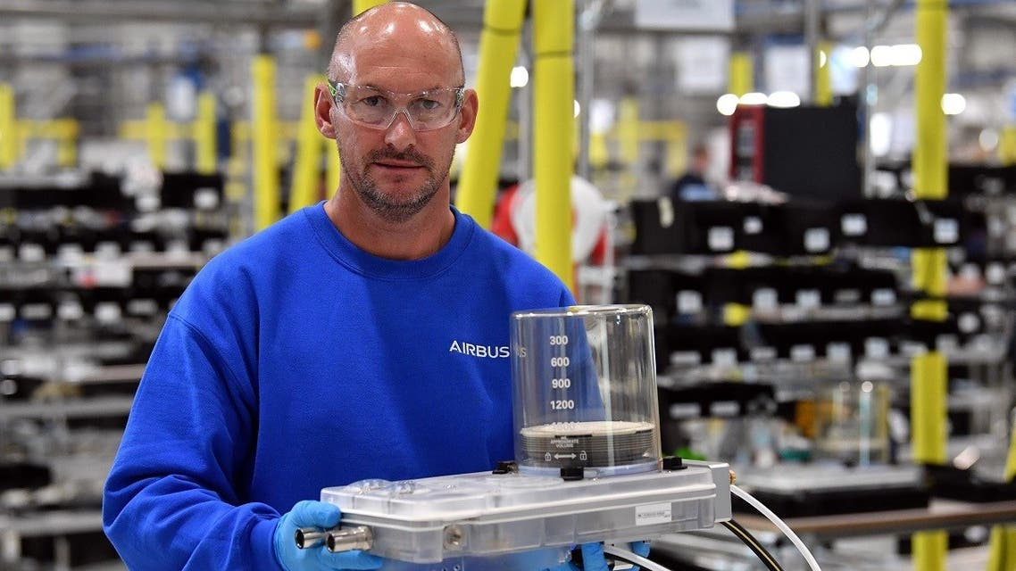 An Airbus employee poses with a completed unit from the assembly line to produce ventilators at the Advanced Manufacturing Research Centre (AMRC Cymru) in Broughton, north Wales on April 30, 2020. (Reuters)