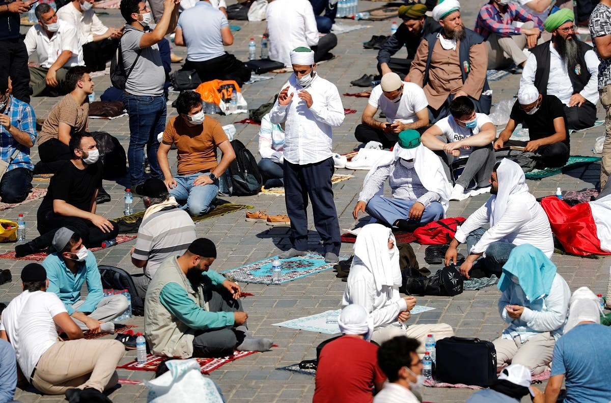 People stand and sit outside Hagia Sophia Grand Mosque as they wait for the beginning of Friday prayers. (Reuters)