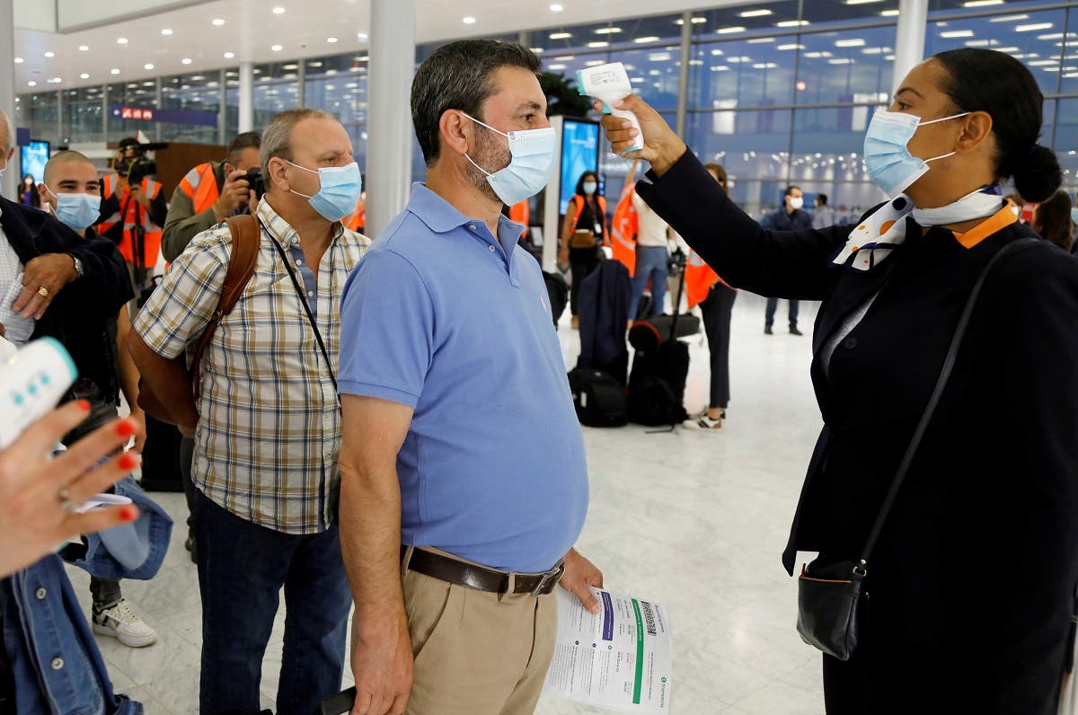 A stewardess takes the body temperature of a man at Paris-Orly Airport  following the coronavirus outbreak in France. (File photo: Reuters)