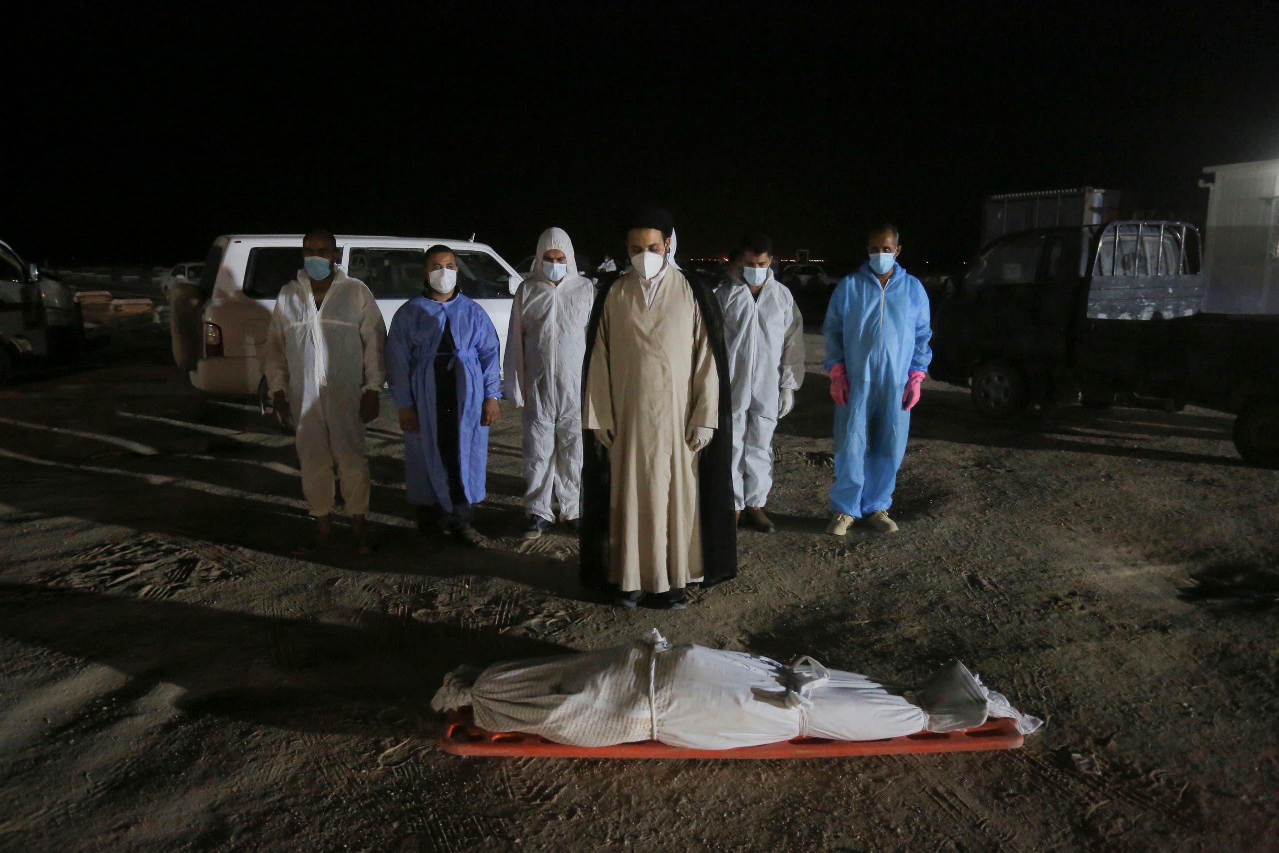 Shiite cleric prays by the body of coronavirus victim at Wadi al-Salam cemetery near Najaf, Iraq, Sunday, July 19, 2020. (AP)