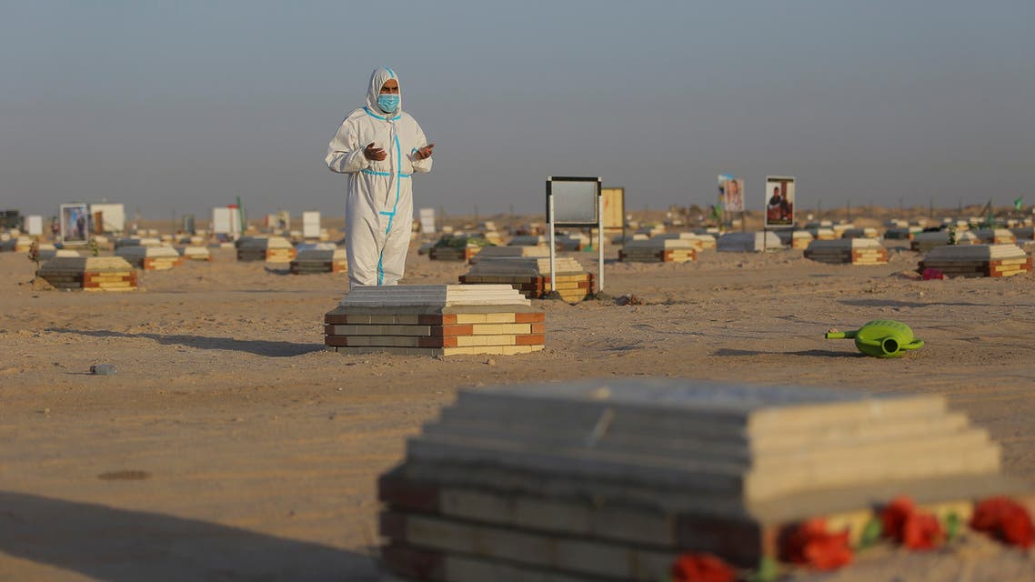 A member the Shiite of Imam Ali brigades militia prays by a grave of a coronavirus victim during a funeral at Wadi al-Salam cemetery near Najaf, Iraq, Monday, July 20, 2020. (AP)