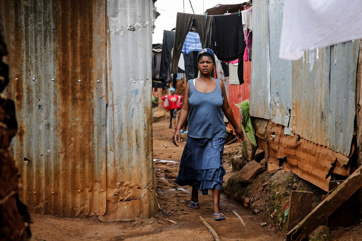 Traditional birth attendant Emily Owino walks down an alley near her home, where she assists women in delivering babies, in the Kibera slum of Nairobi, Kenya Friday, July 3, 2020. (AP)