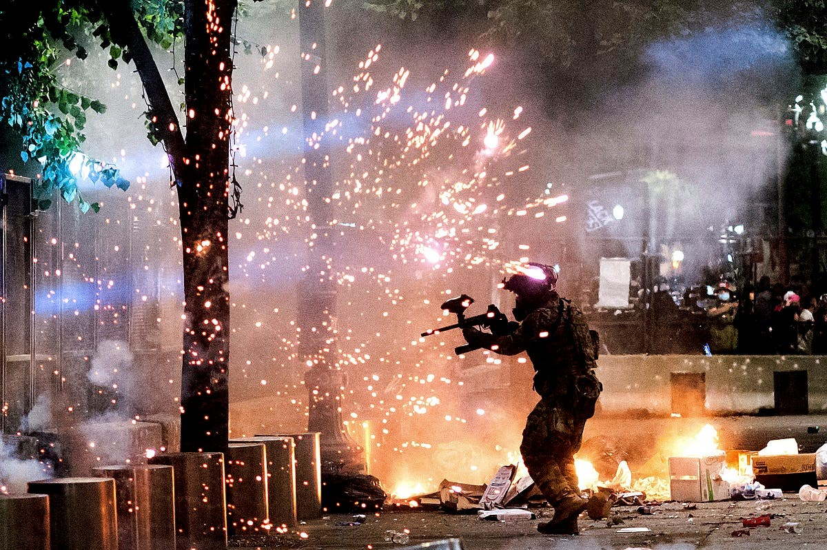 A federal officer fires crowd control munitions at Black Lives Matter protesters at the Mark O. Hatfield United States Courthouse on Friday, July 24, 2020, in Portland, Oregon. (AP)