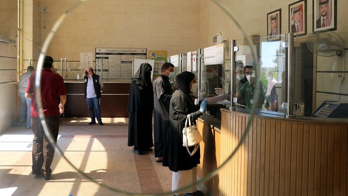 People wearing protective face masks wait to complete their paper work in the Civil Status Department after Jordan's public sector employees returned gradually to work. (File photo: Reuters)
