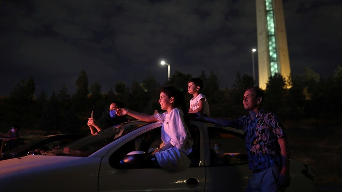 An Iranian family sits in their car while watching a drive-in circus, following the outbreak of the coronavirus disease, in Tehran, Iran, on July 22, 2020. (Reuters)
