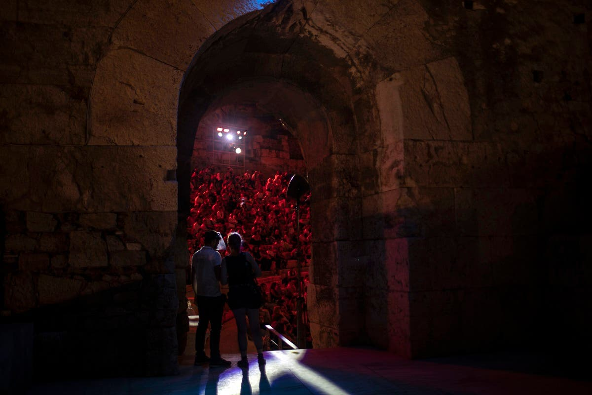 A Steward wearing a plastic visor stands at a gate of the Odeon of Herodes Atticus in Athens, during a concert. (AP)