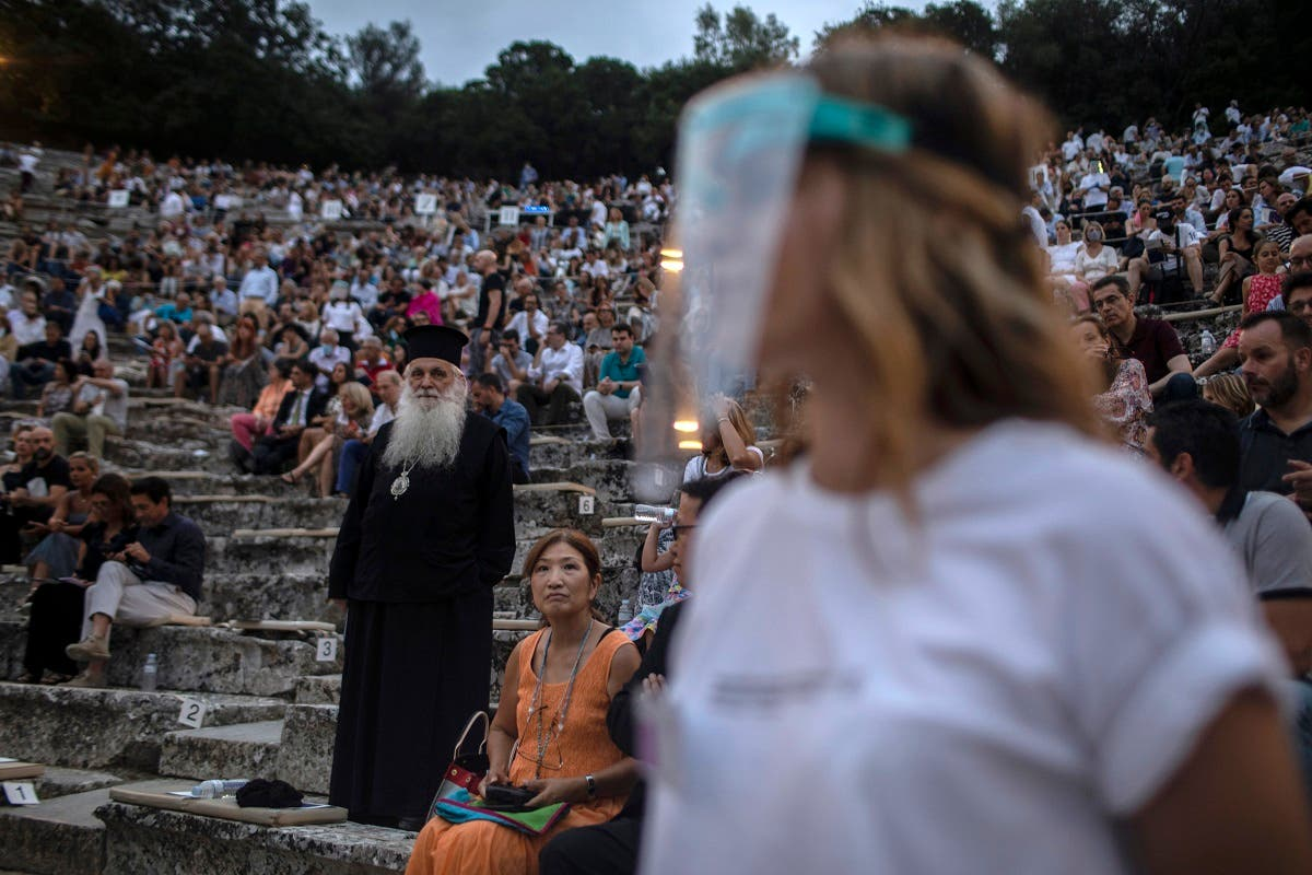A steward wearing plastic visor stands in front of a Greek Orthodox priest as spectators take their seats at the ancient theater of Epidaurus, Greece. (AP)