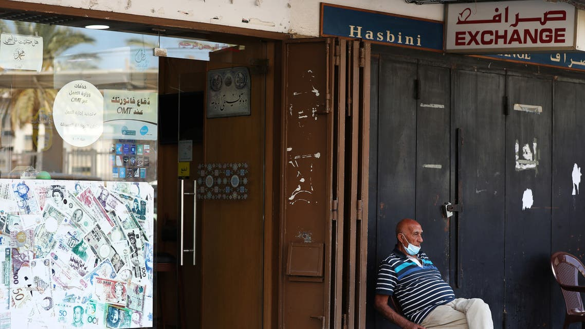 A man sits outside of a currency exchange shop in Beirut, Lebanon June 15, 2020. (Reuters)