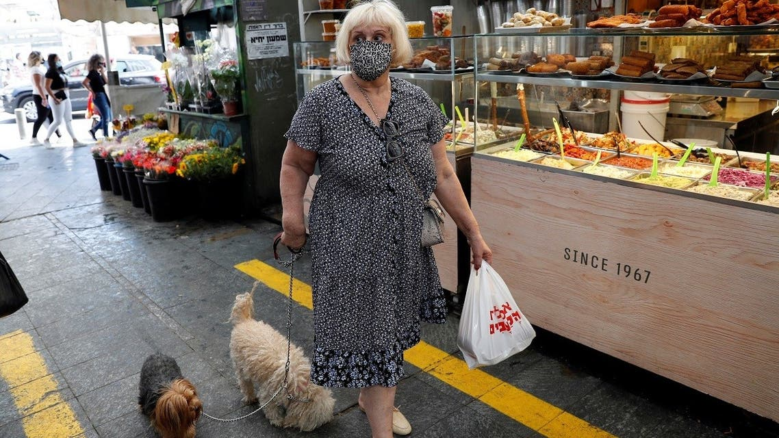 A woman wears a face mask as she walks with her dogs in a main market in Jerusalem on July 16, 2020. (Reuters)2020-07-17T042242Z_1193398852_RC2SUH9W4TFT_RTRMADP_3_HEALTH-CORONAVIRUS-ISRAEL