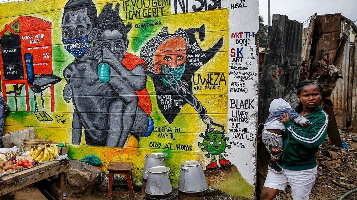 A woman carries a baby past an informational mural warning people about the dangers of the new coronavirus and how to prevent transmission, with words in Swahili reading We are the Cure, painted by youth artists from the Uweza Foundation, in the Kibera slum, or informal settlement, of Nairobi, Kenya Wednesday, July 8, 2020. (AP)