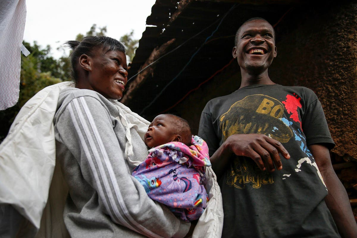 Mother Veronica Atieno, left, holds her daughter Shaniz Joy Juma, center, delivered a month earlier by a traditional birth attendant during a dusk-to-dawn curfew, accompanied by her husband Gabriel Owour Juma, right, in the Kibera slum of Nairobi, Kenya Friday, July 3, 2020. (AP)