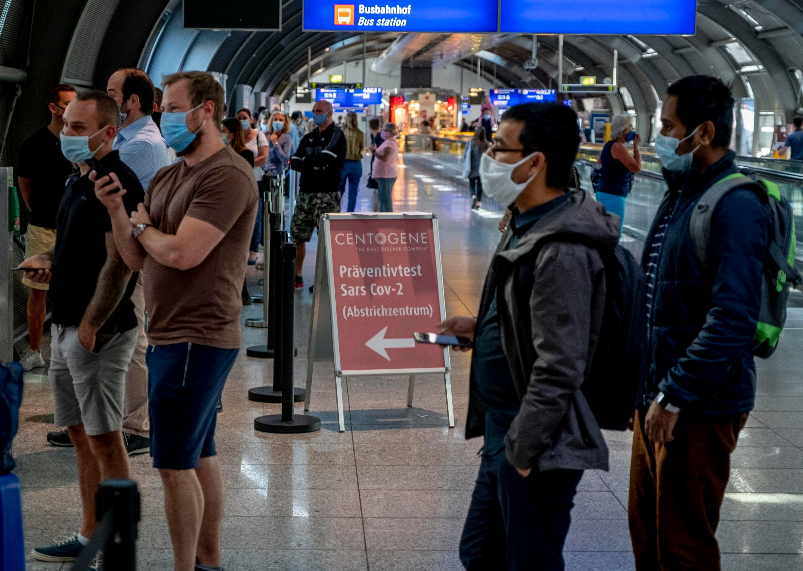 Dozens of passengers from various countries queue at the Centogene test center for a Covid-19 test at the airport in Frankfurt, Germany on July 24, 2020. (AP)