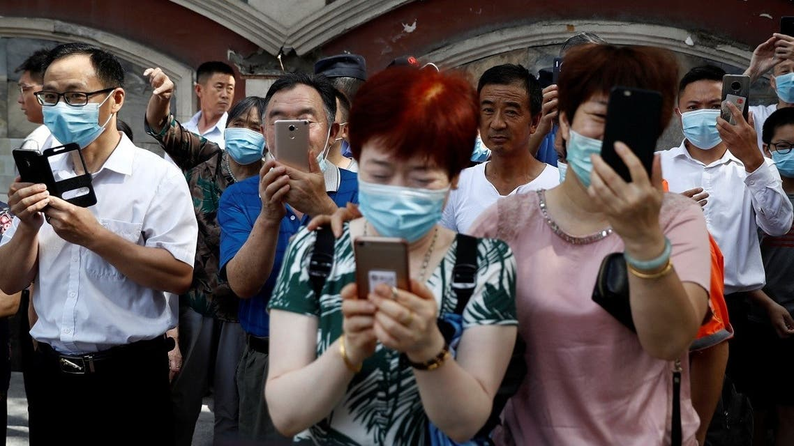 People take pictures of a bus, which US Consulate staff loaded up in the morning, as it leaves the US Consulate General in Chengdu, Sichuan province, China, on July 26, 2020. (Reuters)