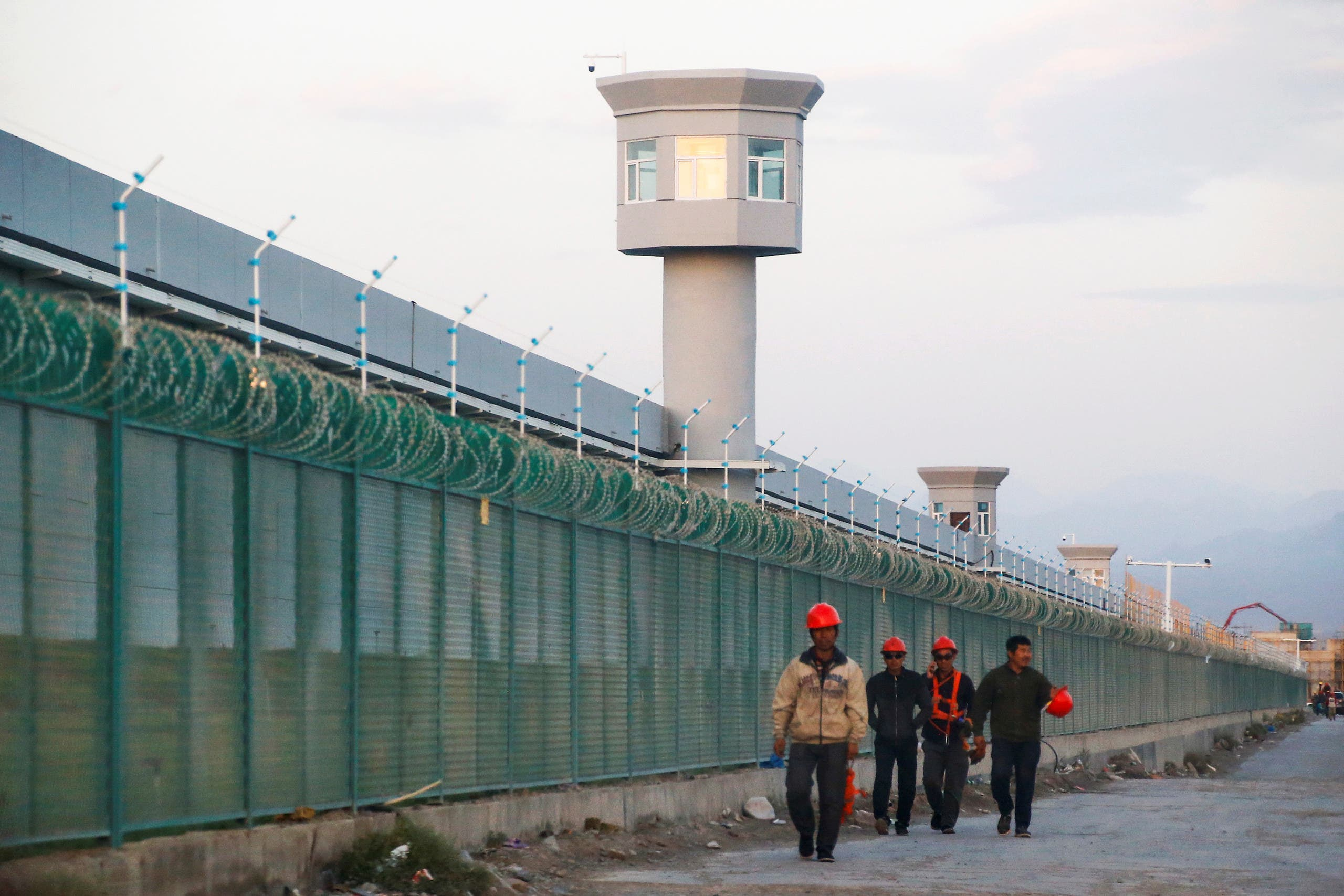Workers walk by the perimeter fence of what is officially known as a vocational skills education center in Xinjiang Uighur Autonomous Region, China on September 4, 2018. (AP)
