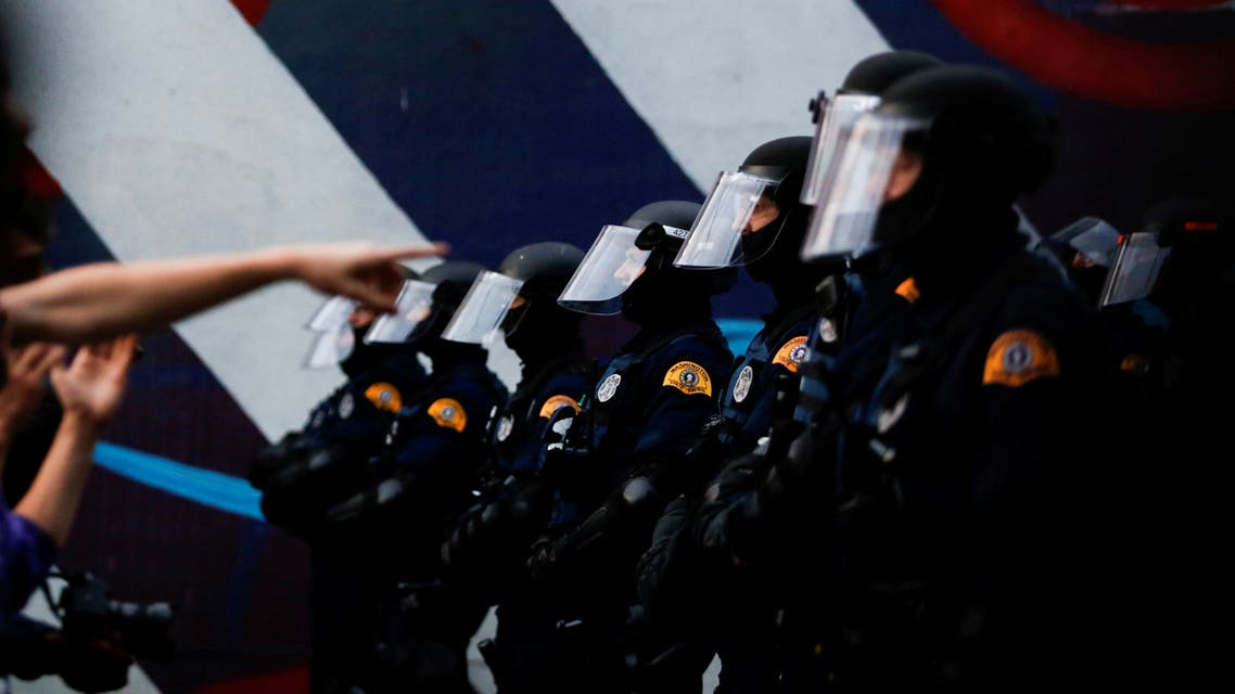 A line of Washington State Patrol officers in riot gear form as protesters point over a barricade during a protest against police brutality and the death in Minneapolis police custody of George Floyd, near Seattle Police Department's East Precinct in Seattle. (Reuters)