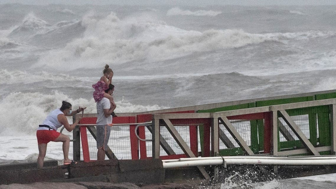 A girl covers her face from strong winds as her family members watch high swells from Hurricane Hanna from a jetty in Galveston, Texas, US, on July 25, 2020. (Reuters)