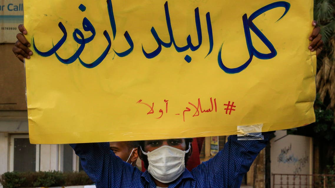 A mask-clad demonstrator (due to the COVID-19 coronavirus pandemic) stands with a sign reading in Arabic all of the country is Darfur, #PeaceFirst, during a protest outside the Sudanese Professionals Association in the Garden City district of Sudan's capital Khartoum on July 4, 2020, in solidarity with the people of the Nertiti region of Central Darfur province in the country's southwest. Hundreds of Sudanese had held a protest the previous day in the Central Darfur state calling on the government to secure their properties following recent incidents of killings and looting. A week prior, unidentified armed men killed three farmers near the town of Nertiti in Central Darfur, triggering the ire of residents who long complained of lack of security in the area.