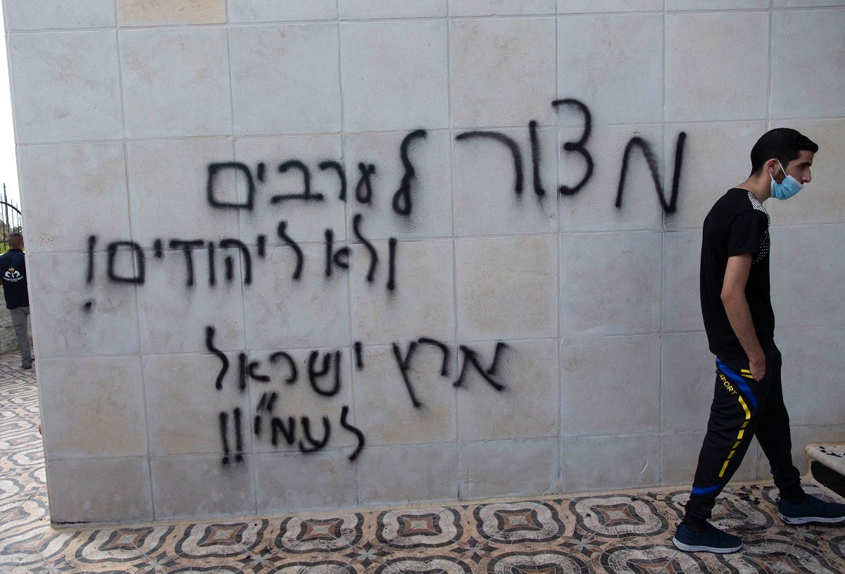 A Palestinian man walks by a wall spray painted with anti-Palestinian slogans in Hebrew that read, a siege on the Arabs, not on the Jews, the land of Israel is for Israelis, at a mosque in el-Bireh, near the West Bank city of Ramallah, Monday, July 27, 2020. (AP)