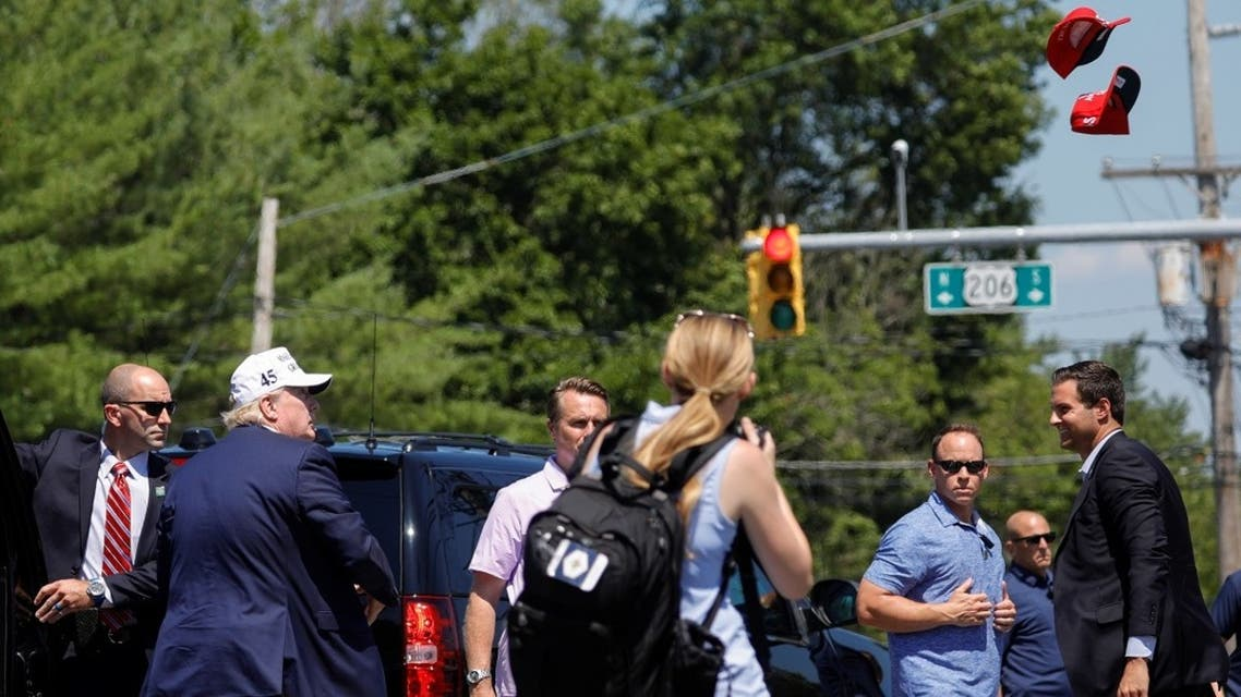 US President Donald Trump tosses campaign hats to supporters during a roadside stop in New Jersey, US, July 26, 2020. (Reuters)
