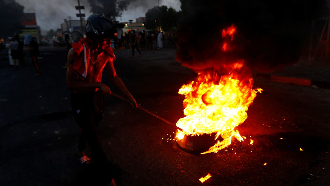 An Iraqi demonstrator burns tires to block the road during a protest over poor public services in the holy city of Najaf, Iraq July 26, 2020. REUTERS/Alaa Al-Marjani