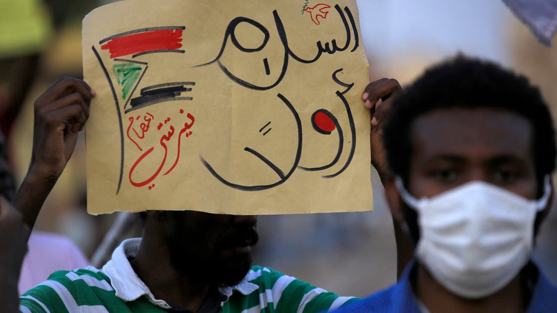 A demonstrator holds up a sign reading in Arabic peace first, Nertiti sit-in along with a drawn Sudanese flag, during a protest outside the Sudanese Professionals Association in the Garden City district of Sudan's capital Khartoum on July 4, 2020, in solidarity with the people of the Nertiti region of Central Darfur province in the country's southwest. Hundreds of Sudanese had held a protest the previous day in the Central Darfur state calling on the government to secure their properties following recent incidents of killings and looting. A week prior, unidentified armed men killed three farmers near the town of Nertiti in Central Darfur, triggering the ire of residents who long complained of lack of security in the area.