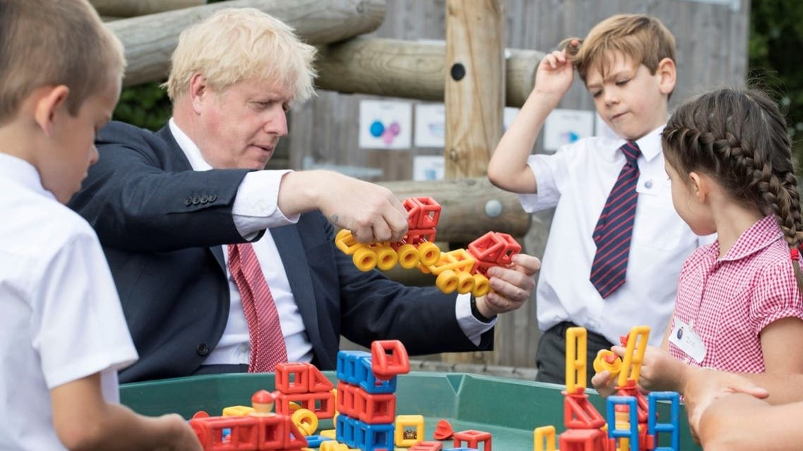 Britain's Prime Minister Boris Johnson plays with toys as students look on during a visit to The Discovery School in Kent, Britain, on July 20, 2020. (Reuters)