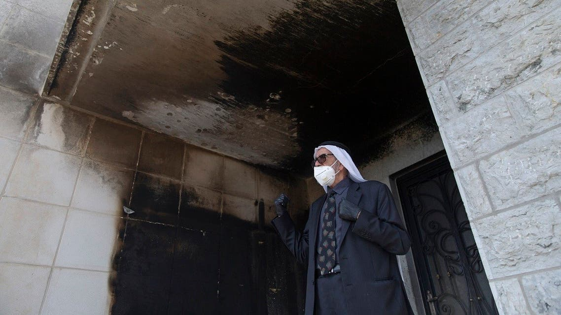 A Palestinian man inspects burned walls of a mosque at el-Bireh, near the West Bank city of Ramallah, Monday, July 27, 2020. (AP)