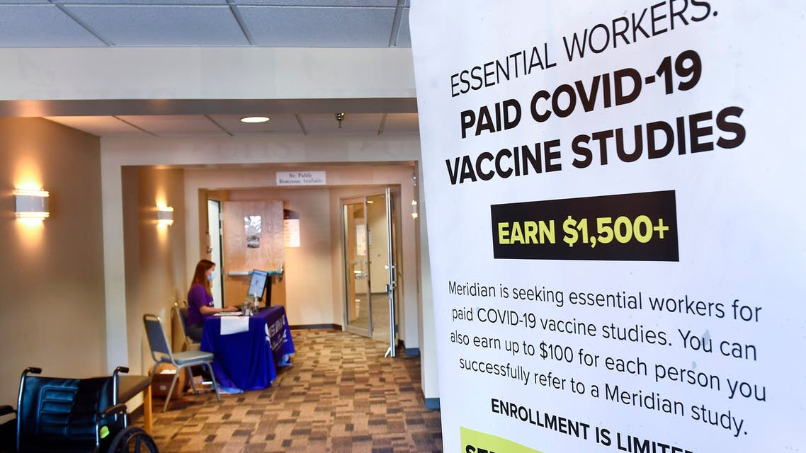 A poster is displayed in the entrance way looking for volunteers as the world's biggest study of a possible COVID-19 vaccine, developed by the National Institutes of Health and Moderna Inc., gets underway Monday, July 27, 2020, in Binghamton, N.Y. (AP Photo/Hans Pennink)