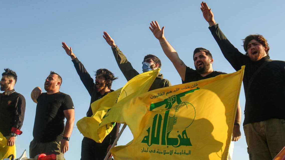 Supporters of the Lebanese Shiite movement Hezbollah perform a salute as they stand behind motorcycles carrying the group's flags in the southern Lebanese district of Marjayoun on the border with Israel on May 25, 2020. Twenty years after the withdrawal of Israeli forces from Lebanon, Hezbollah still enjoys wide support among youth regaled with tales of the Shiite group ending 22 years of Israeli occupation.