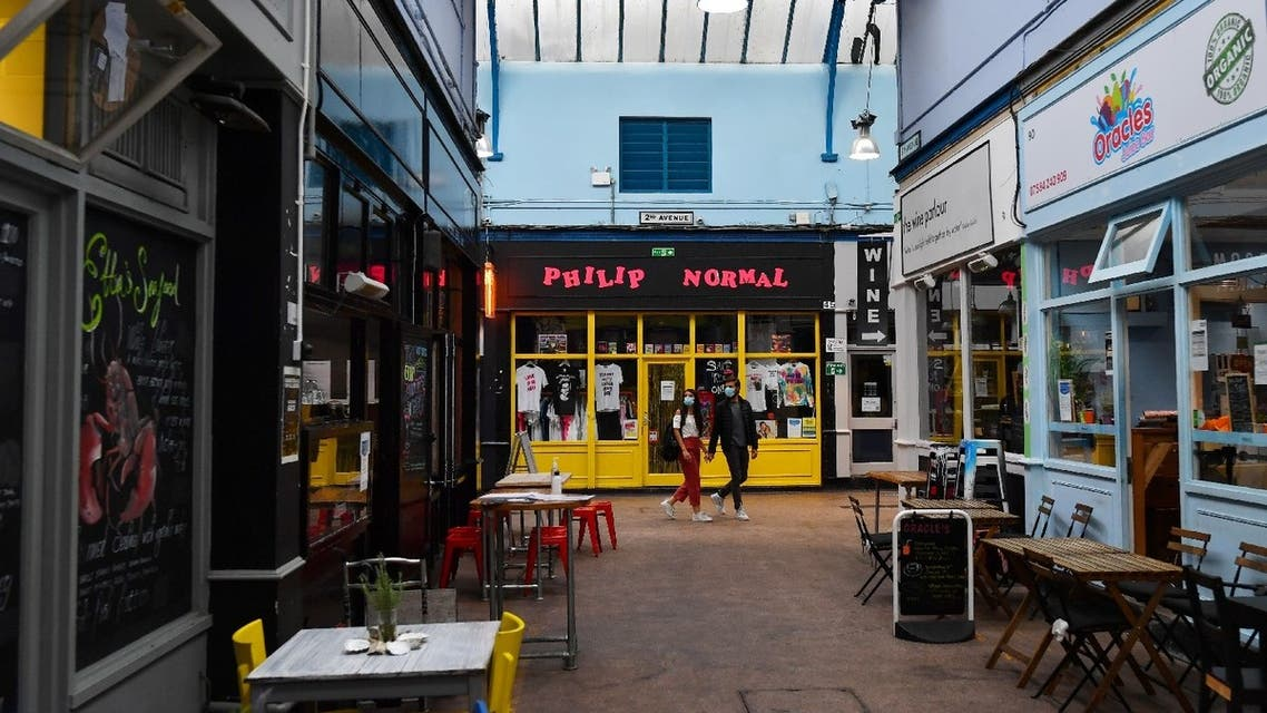A couple walk past empty restaurants, as the outbreak of the coronavirus continues to affect businesses, in London, Britain, July 14, 2020. (Reuters)