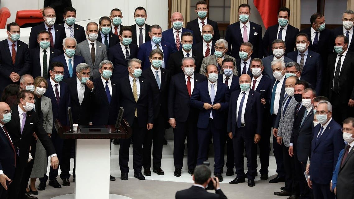 Turkey's ruling Justice and Development (AK) Party Tekirdag Deputy Mustafa Sentop (cnetere red tie) poses with deputies, all wearig a protective face mask, at the General Assembly after being re-elected as the Speaker of the Turkish Parliament in Ankara, Turkey on July 7, 2020. (AFP)