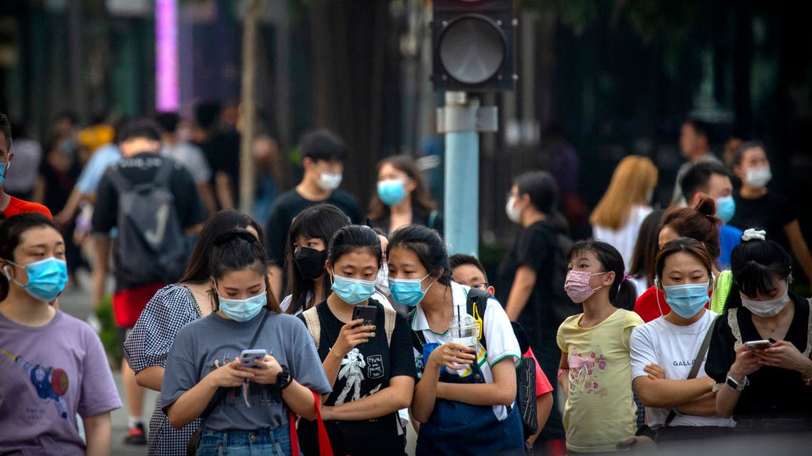 People wearing face masks to protect against the coronavirus wait to cross an intersection in Beijing on July 29, 2020. (AP)