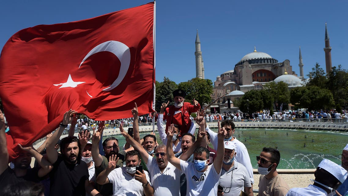 Turkish people, one holding a flag, chant slogans outside the Hagia Sophia on July 24, 2020. (AP)