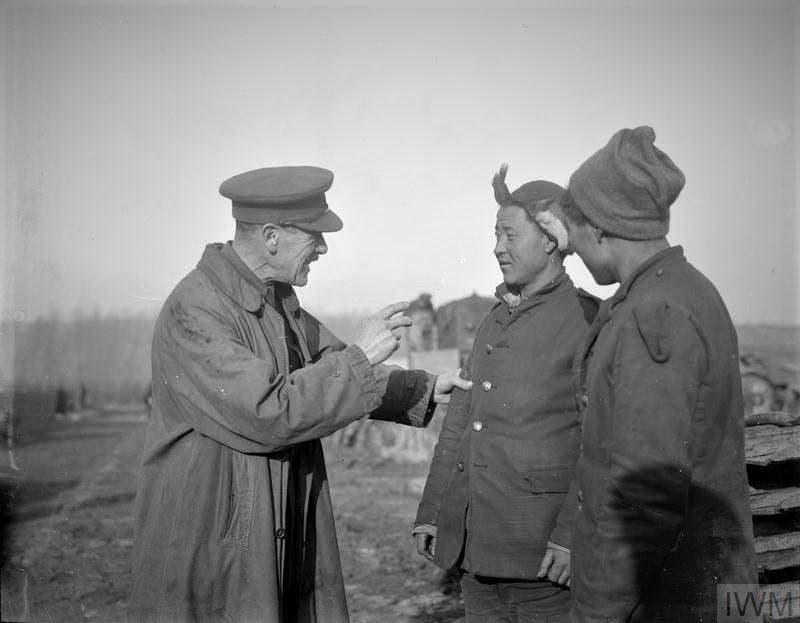 عمال صينيون أثناء تلقيهم لتعلليمات من قبل مسؤول بريطاني