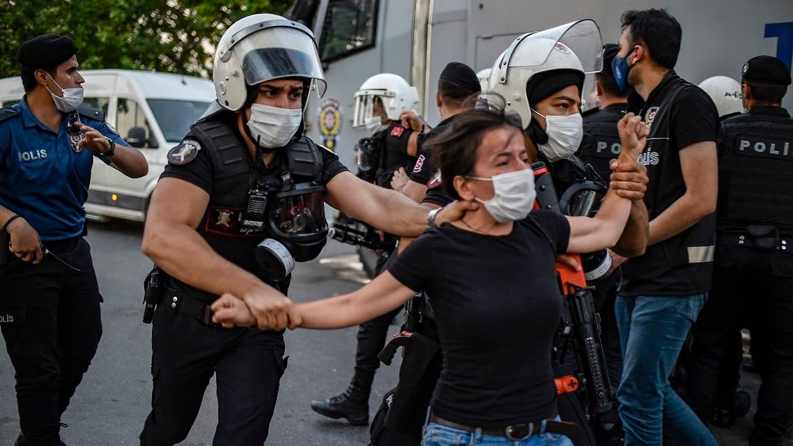 Policemen detain a woman during a protest to mark the anniversary of the 2015 suicide attack in the southern Turkish town of Suruc, in the Kadikoy district of Istanbul on July 20, 2020. (AFP)