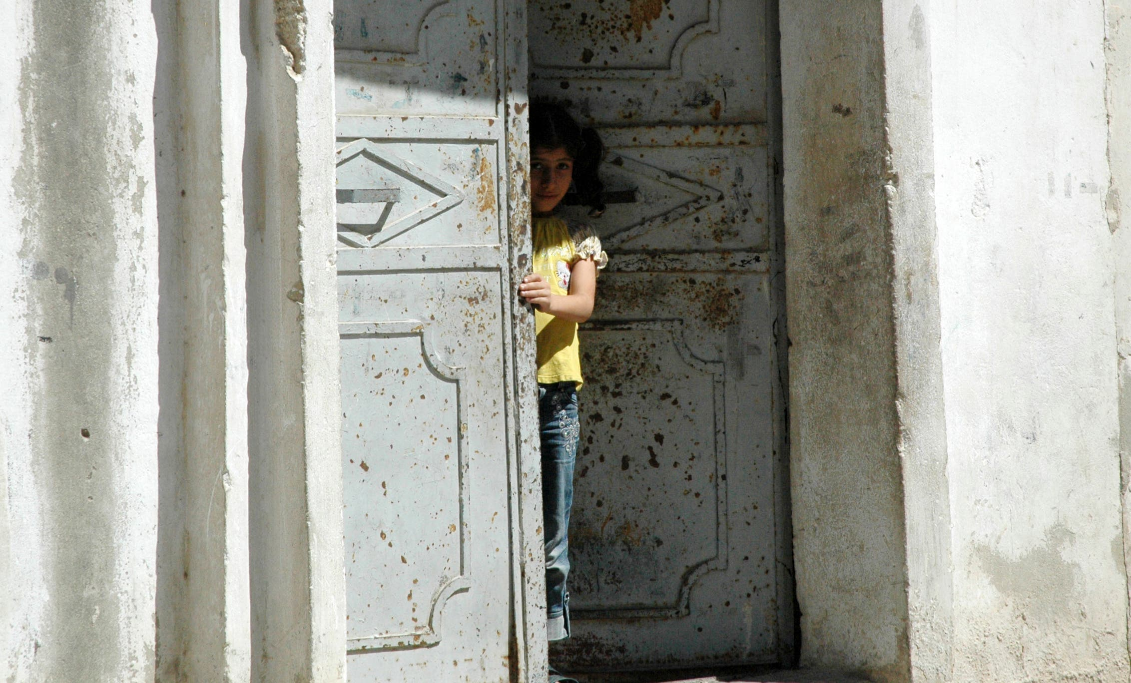 A Syrian girl peers from the entrance of her home in Hama on August 11, 2011. (AFP)