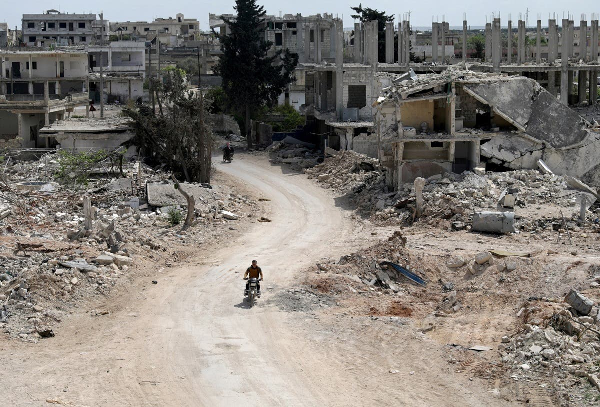 A man rides a motorbike past damaged buildings in the rebel-held town of Nairab, Idlib region, Syria April 17, 2020. (File Photo: Reuters)