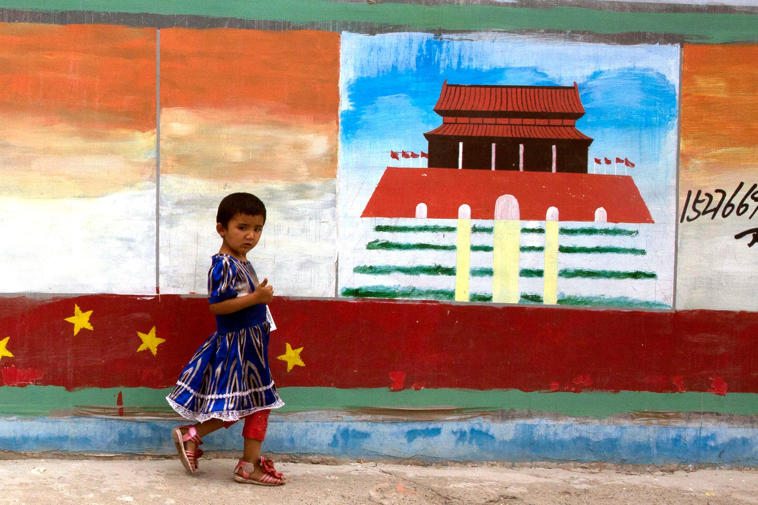 A Uighur child walks past a mural depicting China's Tiananmen Gate on the streets of Aksu in western China's Xinjiang province. (File photo: AP)