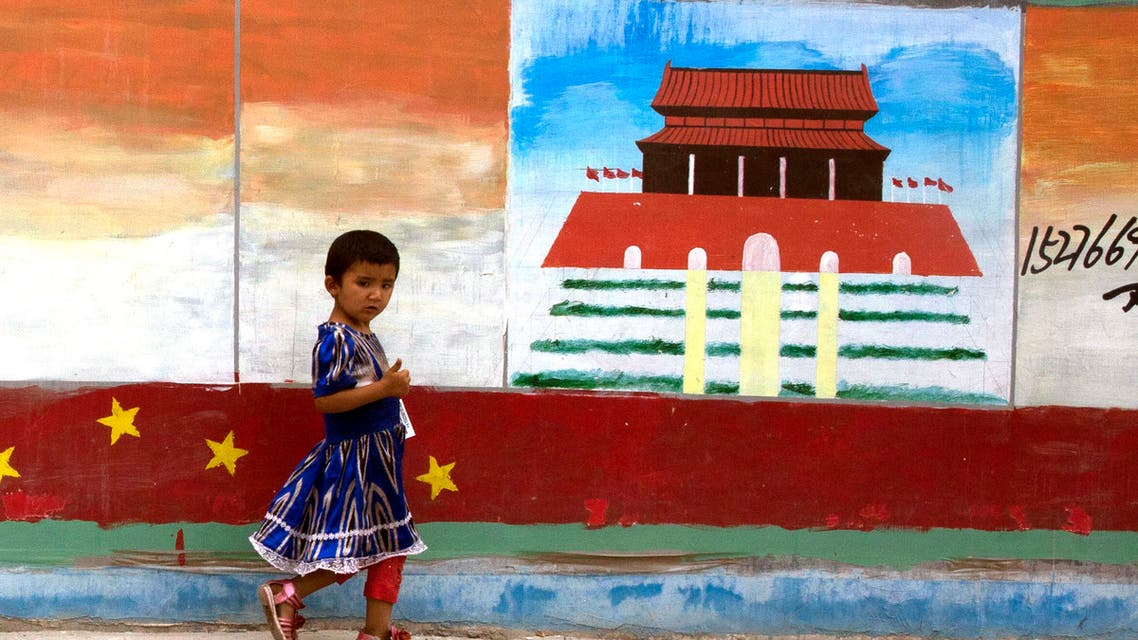 A Uighur child walks past a mural depicting China's Tiananmen Gate on the streets of Aksu in western China's Xinjiang province on July 17, 2014. (AP)