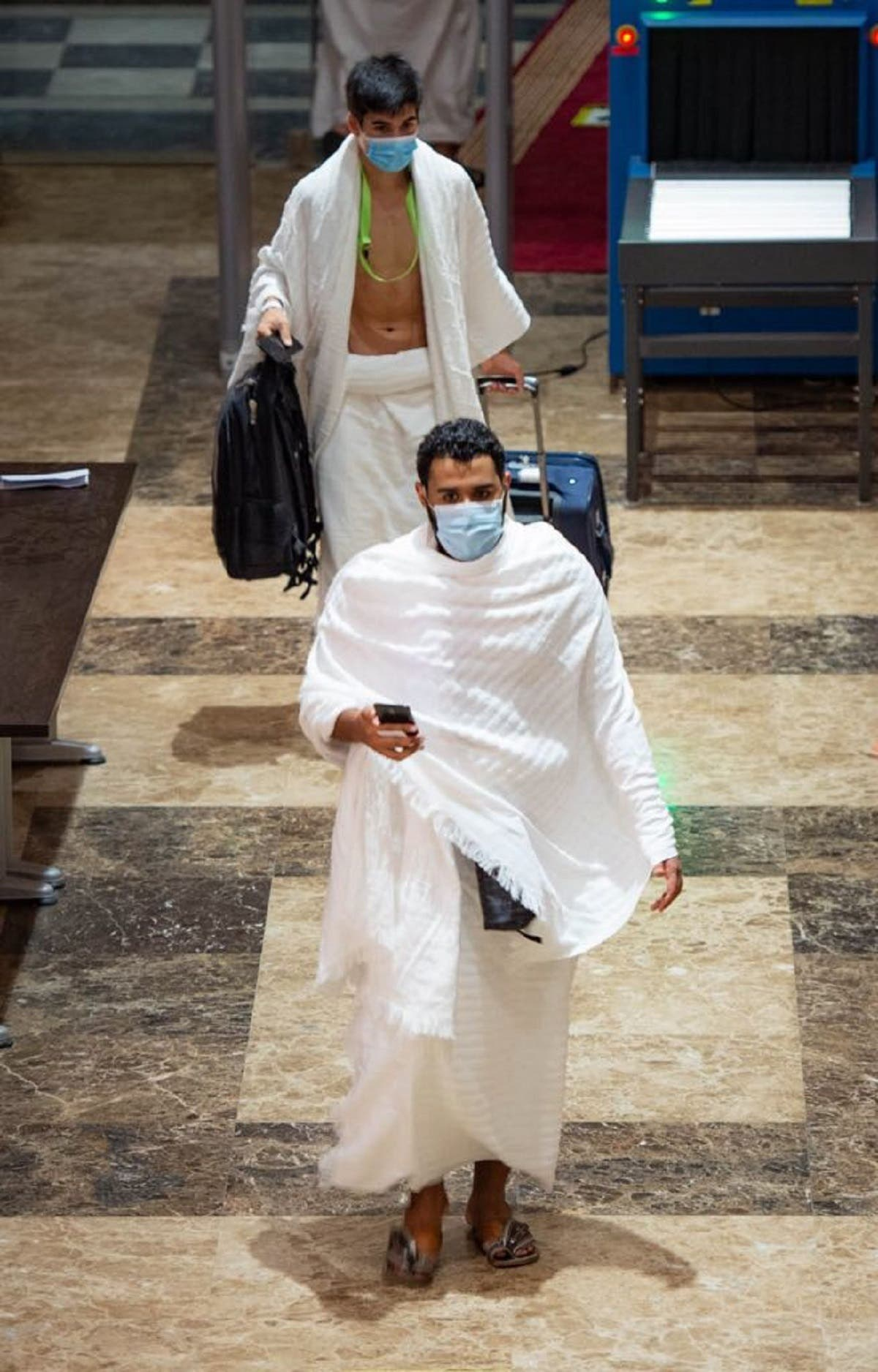Hajj pilgrims depart from the hotel amid strict coronavirus measures. (SPA / Twitter)
