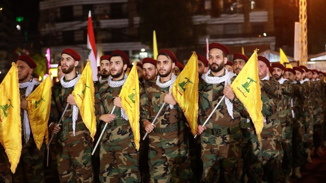 Fighters with the Lebanese Shia Hezbollah group, carry flags as they parade in a southern suburb of the capital Beirut, on May 31, 2019. (AFP)
