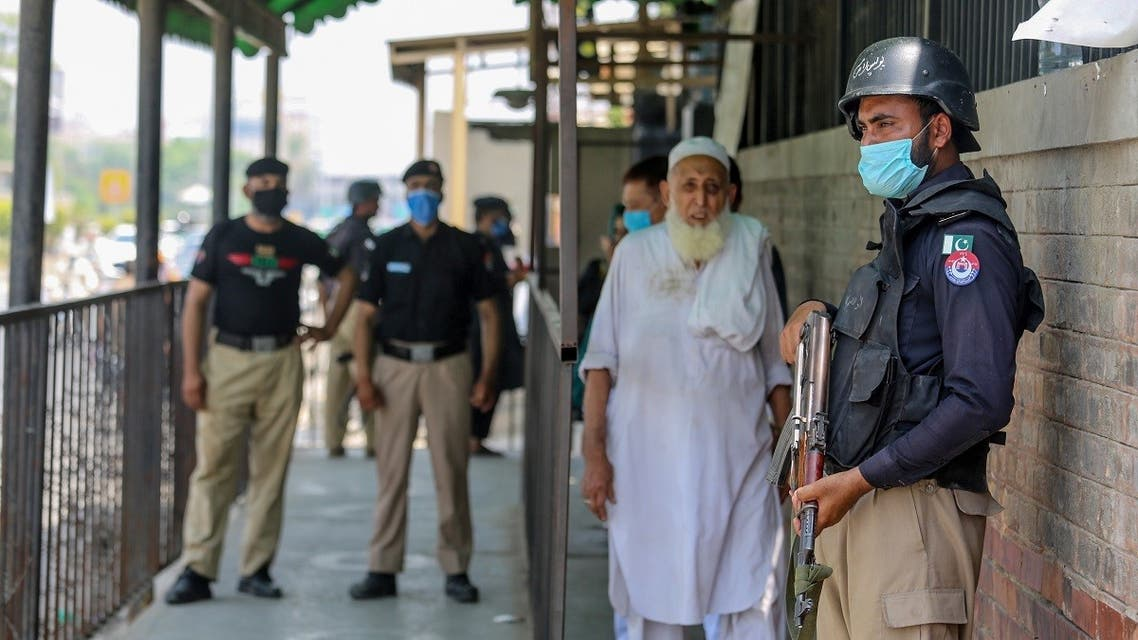 Security personnel (L and R) stand guard outside the district court building following the killing of a man allegedly accused of blasphemy in Peshawar on July 29, 2020. (AFP)